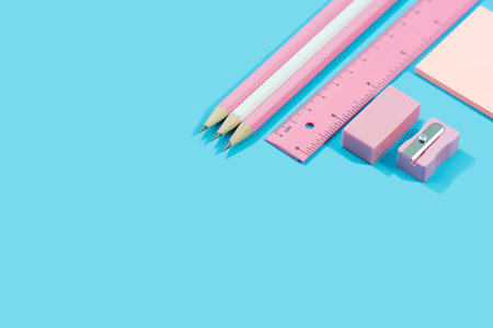 Stationary concept Flat Lay.  Stationary about pencils, paper note, ruler, rubber and Pencil sharpener pastel tone on blue background with copy space.