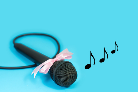 Microphone with pink ribbon and musical note on blue background. Stock Photo