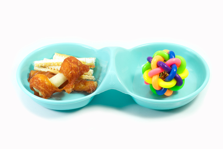 Pet supplies about plastic bowl with snacks and rubber toys for dog on white background.