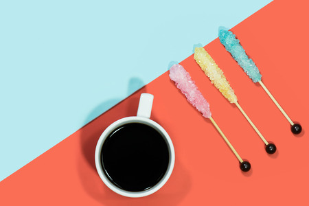 Sugar crystal on wooden stick with hot coffee on red and blue background. Imagens
