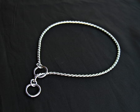Silver or stainless choke chain for dog isolated on black background