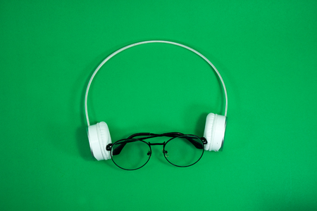Glasses and white headphones on a green background.