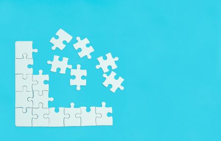 White jigsaw of puzzle on blue background.