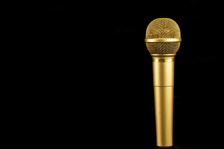 Golden microphone on black background. Фото со стока