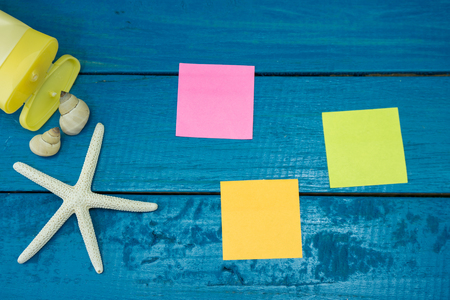 Post it note and star fish on wooden background.  Summer holiday concept.