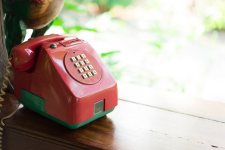 Retro red telephone on wood table. Banque d'images
