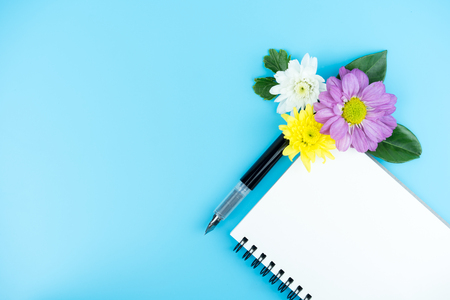 Blank notebook with Ink pen and decorate flowers and green leaf on color background