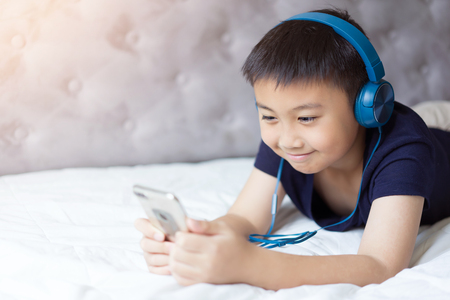 Little boy listening to music on bed at bedroom for relax