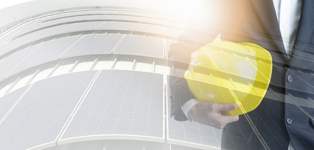 Engineer with safety helmet on solar energy background. Business about Natural energy concept. Double exposure