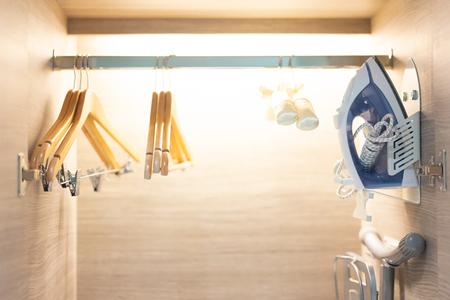 Wooden wardrobe with Hanger on rail in walk in closet design interior.