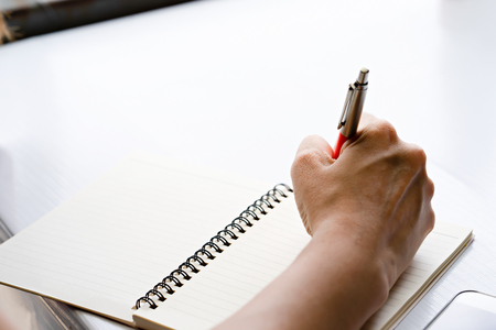 Hand holding a pen for write on notebook