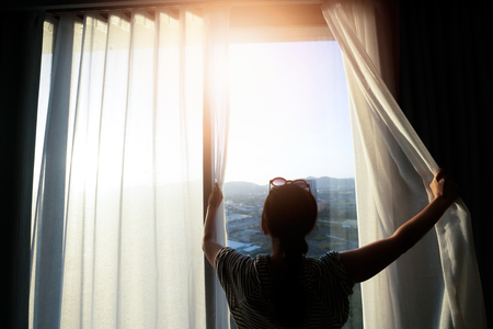 Beautiful woman is opening the curtain at the window in the morning.