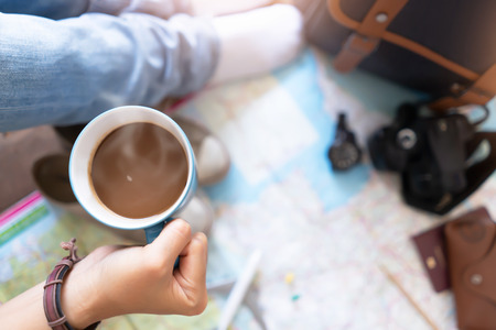 Hand hold coffee and planning for travel Reklamní fotografie