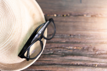 Eyeglasses and hat on wooden background