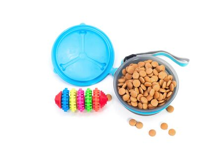 Pet accessories concept.  Pet bowl with dry food and toy on isolated white background. 写真素材