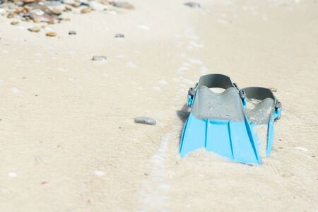 Blue fins for snorkel on the beach at the sea.