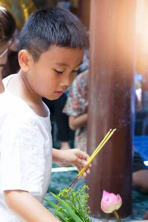 Little boy burning incense for Buddha