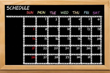Schedule with grid time table on black chalkboard background Stock fotó