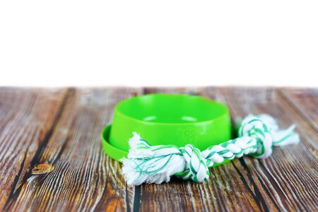Pet accessories concept.  Pet bowl with toy on wooden with copy space.