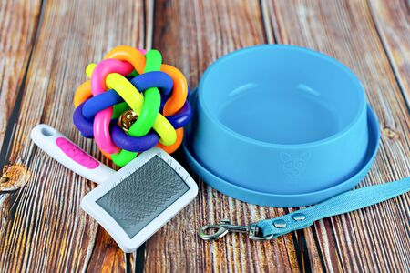 Pet accessories concept.  Pet leashes with rubber toy and bowl on wooden background.
