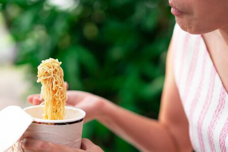 Woman eating noodles cup with a Plastic Fork