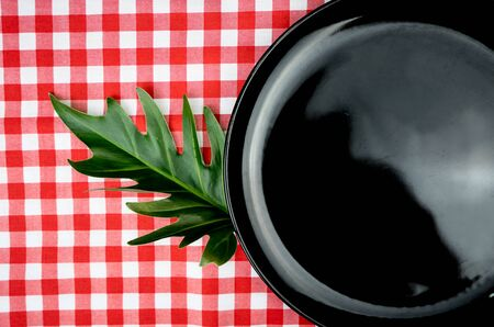 Blank black plate or dish on dinner table with copy space