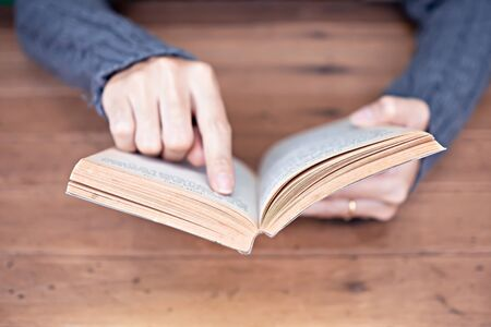 Hand holding a book at home