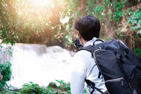 Professional photographer photographing waterfalls in the forest