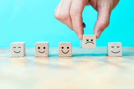 Businessman chooses a emoticon icons sadly on wooden block , Business bad teamwork concept