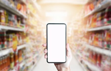Using smartphone for shopping online on abstract supermarket background.  Business online concept
