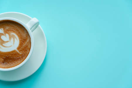 Hot coffee with late art on blue background