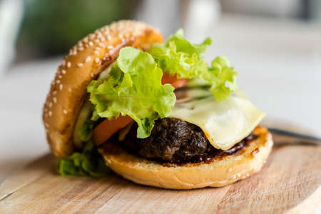 Hamburger on the wooden plate. Fast food concept