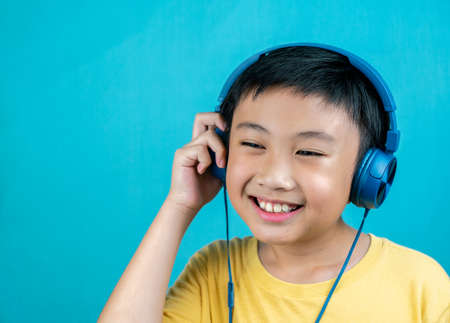 Little boy listening to music on blue background