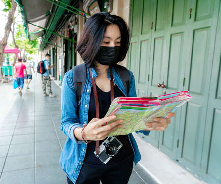 Women wearing health mask look a map for travel at the city