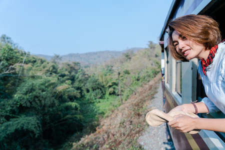 Woman looks out from window traveling by train