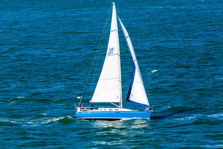 San Francisco, CA, USA - May 21, 2016:  Blue sailboat cruising in the San francisco Bay.