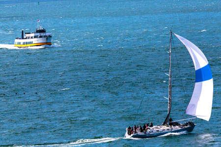 San Francisco, CA, USA - May 21, 2016:  A sailboat and a passnger ferry boat cruising on the San Francisco Bay.