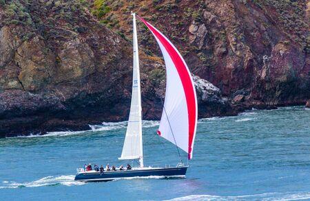 San Francisco, CA, USA - May 21, 2016:  A blue sailboat with a red and white sail cruising in San Francisco. Editöryel