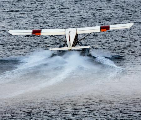 Ketchikan, AK, USA - May 24, 2016:  A seaplane revs spray for an aquatic take off.
