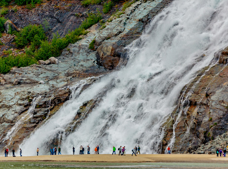 Juneau, AK, USA - May 25, 2016:  Visitors watch the majesty of Nugget Falls located adjacent to the Mendenhall Glacier. 新聞圖片