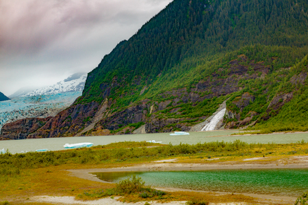 nugget: Juneau, AK, USA - May 25, 2016:  Panorama of the moraine and blue ice of the Mendenhall Glacier, Mendenhall Lake, Nugget Falls and floating icebergs.