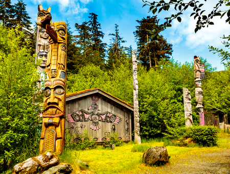 tlingit: Ketchikan, AK, USA - May 24, 2016:  Native American Totems and Clan Houses located at Totem Bight State Historic Site.