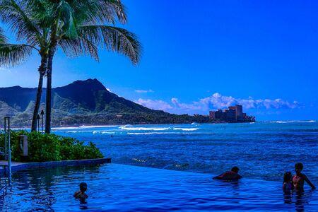Waikiki , Oahu,  Hawaii, USA - September 4, 2015:  Tourists enjoy a dip in the pool while overlooking Waikiki Beach and Diamond Head crater.