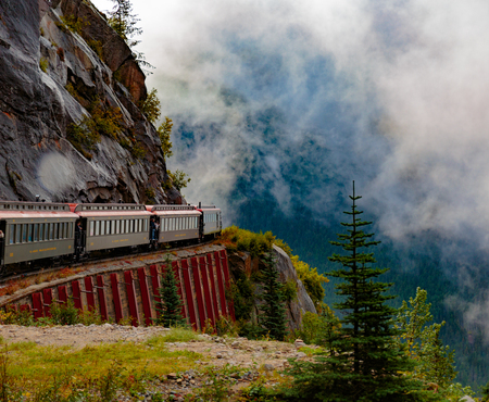 alaska scenic: Skagway, Alaska, USA - September 13, 2016:  This historic railroad system makes daily scenic excursions over rugged terrain overlooking mountains, gorges, glaciers, waterfalls, forests, trestles and tunnels.