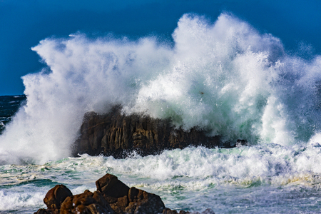 Pebble Beach, California: Wave action on a clear and blustery day produces water explosions against the rocky outcroppings