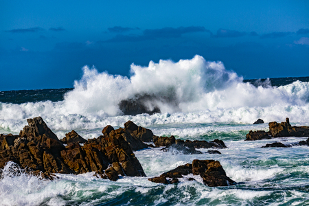 Pebble Beach, California, February 19, 2018:  Wave action on a clear and blustery day produces water explosions against the rocky outcroppings