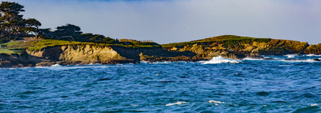 Pebble Beach, California, February 17, 2018:  Panorama view of Fan shell Beach with the Cypress Point Golf Course in the background.