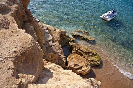 watercraft: Watercraft near the rocky seashore Stock Photo