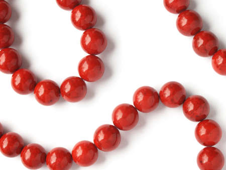 crook: Glossy red coral beads on white background