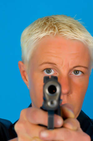 portrait of a beautiful woman with gun in front of a blue background photo